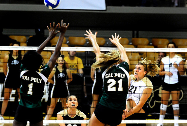 "Becah Fogle, right, spikes the ball toward Dominique Olowolafe, left, and Holly Franks at the CU vs. Cal Poly volleyball game at CU-Boulder on Saturday, Sept. 12, 2009.  More photos at  <a href=""http://www.dailycamera.com"">http://www.dailycamera.com</a>."