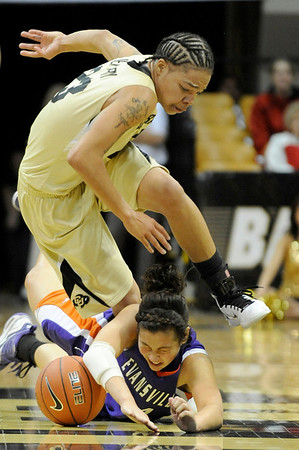 """University of Colorado sophomore Chucky Jeffery jumps over Evansville senior Stephanie Bamberger while trying to steal the ball on Friday, Nov. 26, during a basketball game against the University of Evansville at the Coors Events Center on the CU campus. CU defeated Evansville 55-53.<br /> For more photos go to  <a href=""""http://www.dailycamera.com"""">http://www.dailycamera.com</a><br /> Photo by Jeremy Papasso"""