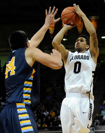 "University of Colorado's Askia Booker takes a shot over Alex Herrera during a game against Fort Lewis College on Friday, Nov. 11, at the Coors Event Center on the CU campus in Boulder. CU won the game 85-57. For more photos of the game go to  <a href=""http://www.dailycamera.com"">http://www.dailycamera.com</a><br /> Jeremy Papasso/ Camera"
