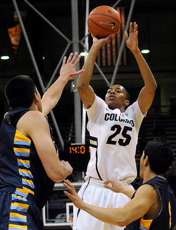 """University of Colorado's Spencer Dinwiddie takes a shot over Fort Lewis defenders during a game against Fort Lewis College on Friday, Nov. 11, at the Coors Event Center on the CU campus in Boulder. CU won the game 85-57. For more photos of the game go to  <a href=""""http://www.dailycamera.com"""">http://www.dailycamera.com</a><br /> Jeremy Papasso/ Camera"""