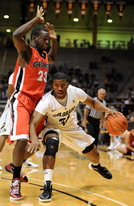 Jremy Adams of Colorado, dribbles into Sherrard Brantley of Georgia,  during the first half of the November 28, 2011 game in Boulder, Co.    November 28, 2011 / Cliff Grassmick