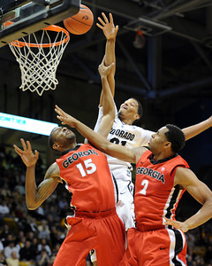 Andre Roberson (21) of Colorado, tries to score over Donte Williams, left, and Marcus Thornton, both of Georgia, during the first half of the November 28, 2011 game in Boulder, Co.  November 28, 2011 / Cliff Grassmick