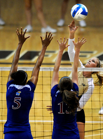 "University of Colorado sophomore Kerra Schroeder tips the ball over the top of Kansas sophomore Tayler Tolefree, No. 5, and junior Nicole Tate, No. 13, on Saturday, Sept. 25, in a volleyball match against the University of Kansas at the Coors Events Center on the CU Boulder campus. CU defeated Kansas 25-23.25-23,13-25,22-25,15-13.<br /> For photo gallery go to  <a href=""http://www.dailycamera.com"">http://www.dailycamera.com</a><br /> Jeremy Papasso/ Camera"