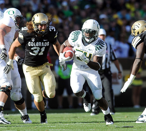 "Kenjon Barner of Oregon runs ahead of Jon Major of CU.<br /> For more photos of the game, go to  <a href=""http://www.dailycamera.com"">http://www.dailycamera.com</a>.<br /> October 22, 2011 / Cliff Grassmick"
