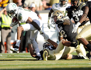 University of Colorado's Terrel Smith holds on to make the tackle on Oregon's Cliff Harris on Saturday, Oct. 22, during a football game against the University of Oregon at Folsom Field in Boulder. CU lost the game 45-2. For more photos go to www.dailycamera.com Jeremy Papasso/ Camera