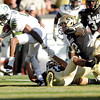 "University of Colorado's Terrel Smith holds on to make the tackle on Oregon's Cliff Harris on Saturday, Oct. 22, during a football game against the University of Oregon at Folsom Field in Boulder. CU lost the game 45-2. For more photos go to  <a href=""http://www.dailycamera.com"">http://www.dailycamera.com</a><br /> Jeremy Papasso/ Camera"