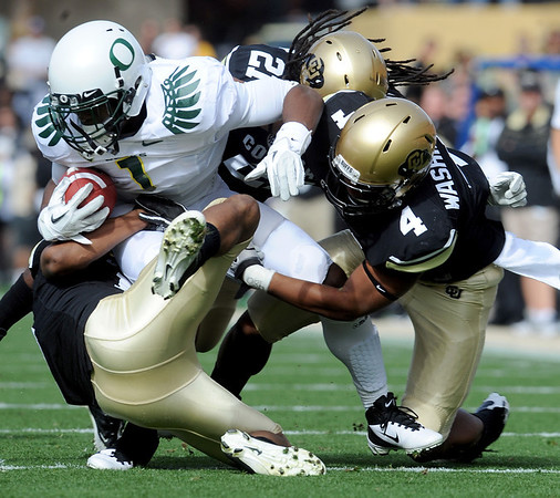 "Josh Huff of Oregon is pulled down by D.D Goodson (21) and Kyle Washington of CU.<br /> For more photos of the game, go to  <a href=""http://www.dailycamera.com"">http://www.dailycamera.com</a>.<br /> October 22, 2011 / Cliff Grassmick"