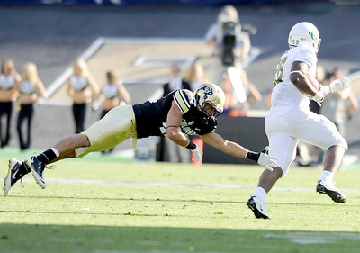 University of Colorado's K.T. Tu'umalo dives and misses a tackle on Oregon's Tra Carson on Saturday, Oct. 22, during a football game against the University of Oregon at Folsom Field in Boulder. CU lost the game 45-2. For more photos go to www.dailycamera.com Jeremy Papasso/ Camera