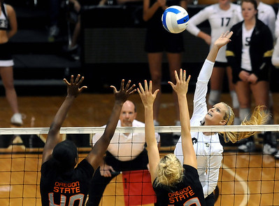 University of Colorado's Kerra Schroeder goes for a kill over Arica Nassar, left, and Megan McBride on Saturday, Sept. 24, during a volleyball game against the Oregon State Beavers at the Coors Event Center on the CU campus in Boulder. For more photos of the game go to www.dailycamera.com Jeremy Papasso/ Camera