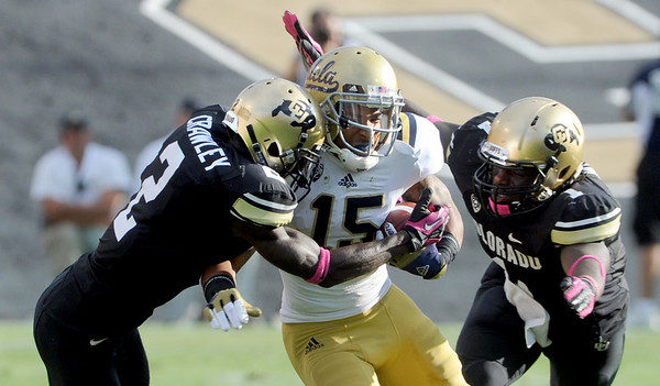 """Kenneth Crawley, left and Derrick Webb, both of CU, try to tackle Devin Lucien of UCLA.<br /> For more photos of the game, go to  <a href=""""http://www.dailycamera.com"""">http://www.dailycamera.com</a><br /> Cliff Grassmick / September 29, 2012"""