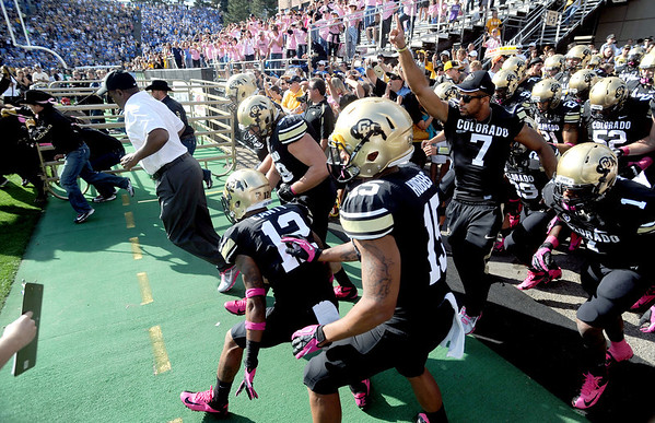 University of Colorado head coach, Jon Embree,  leads his team behind Ralphie for the start of the CU UCLA game.<br /> Cliff Grassmick  / September 29, 2012