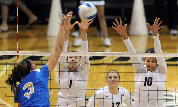 "Tabi Love, left, of UCLA, hits past Kelsey English and Anicia Santos of CU.<br /> For more photos of the game, go to  <a href=""http://www.dailycamera.com"">http://www.dailycamera.com</a><br /> Cliff Grassmick / October 2, 2011"