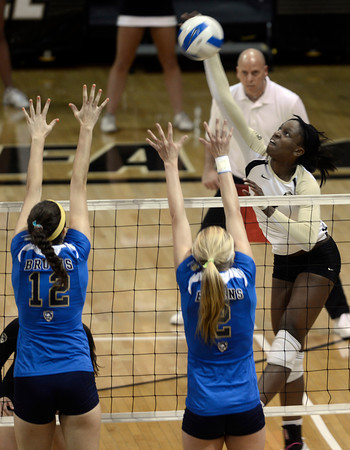 """University of Colorado's Alexis Austin goes for a kill over Nariana Aquino, left,  and Kelly Reeves during a volleyball match against UCLA on Friday, Nov. 9, at the Coors Event Center on the CU campus in Boulder. For more photos of the game go to  <a href=""""http://www.dailycamera.com"""">http://www.dailycamera.com</a><br /> Jeremy Papasso/ Camera"""