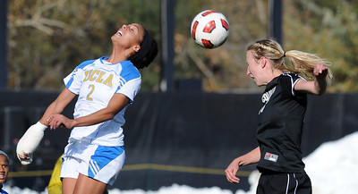 Sydney Leroux, left, of UCLA, and Lizzy Herzl of CU, get up in the air to hit the ball. For more photos of the game, go to www.dailycamera.com. Cliff Grassmick / October 28, 2011