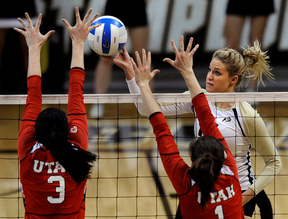 """University of Colorado's Nikki Lindow lobs the ball over the hands of Bailey Bateman, left, and McKenzie Odale for a point during a game against the University of Utah on Wednesday, Sept. 19, at the Coors Event Center in Boulder. For more photos of the game go to  <a href=""""http://www.dailycamera.com"""">http://www.dailycamera.com</a><br /> Jeremy Papasso/ Camera"""