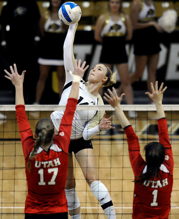"""University of Colorado's Emily Alexis goes for a kill over Erin Redd, left, and McKenzie Odale during a game against the University of Utah on Wednesday, Sept. 19, at the Coors Event Center in Boulder. For more photos of the game go to  <a href=""""http://www.dailycamera.com"""">http://www.dailycamera.com</a><br /> Jeremy Papasso/ Camera"""