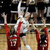 "University of Colorado's Emily Alexis goes for a kill over Erin Redd, left, and McKenzie Odale during a game against the University of Utah on Wednesday, Sept. 19, at the Coors Event Center in Boulder. For more photos of the game go to  <a href=""http://www.dailycamera.com"">http://www.dailycamera.com</a><br /> Jeremy Papasso/ Camera"