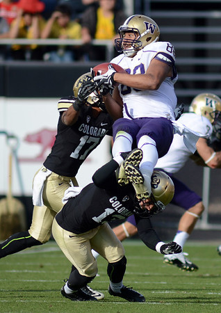 "Austin Seferian-Jenkins of Washington goes up high for a catch and is hit by Marques Mosley and Parker Orms of CU.<br /> For more photos of the CU game, go to  <a href=""http://www.dailycamera.com"">http://www.dailycamera.com</a><br /> Cliff Grassmick / November 17, 2012"
