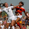 Amy Barczuk, left, of CU and Melinda Mercado of Oklahoma State collide after attacking the ball in front of the OSU net.<br /> Cliff Grassmick / August 22, 2009