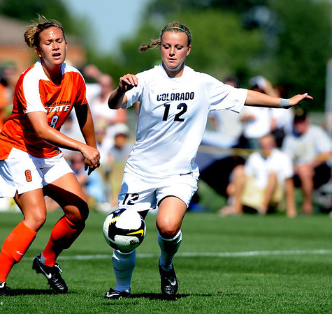 Kelly Butler (12) of CU is about to kick the winning goal against Allyson Leggett of Oklahoma State on Saturday.<br /> Cliff Grassmick / August 22, 2009