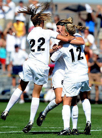 Kelly Butler (12) is mobbed by teammates after kicking what turned out to be the winning goal against Oklahoma State on Saturday.<br /> Cliff Grassmick / August 22, 2009
