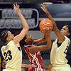 Danielle Robinson, of Oklahoma, puts up a shot on Chucky Jeffery, left, and Brittany Spears both of Colorado, in the first half of the February 23, 2011 game in Boulder.<br /> Cliff Grassmick / February 23, 2011