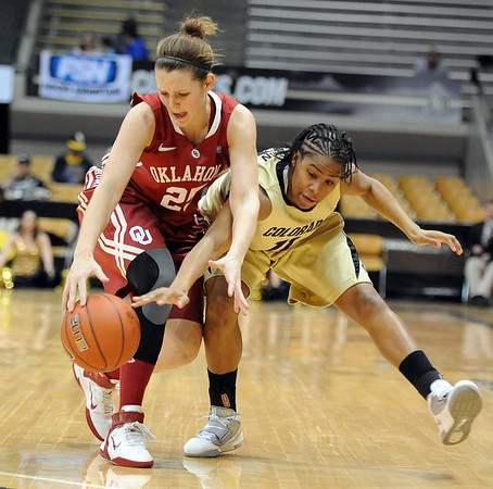 Whitney Hand, left, of Oklahoma, and Brittany Wilson of Colorado, chase down a loose ball in the first half of the February 23, 2011 game in Boulder.<br /> Cliff Grassmick / February 23, 2011
