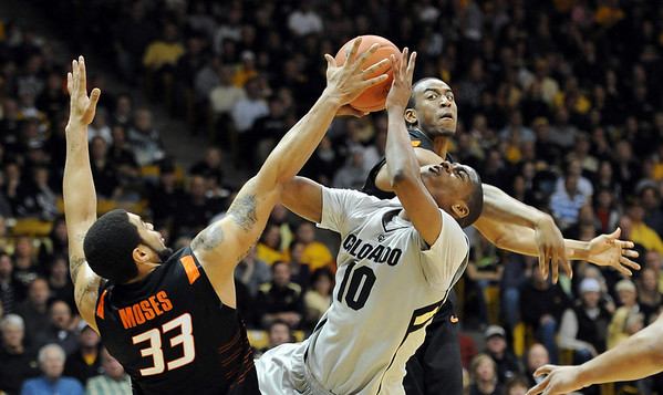 """Alec Burks of Colorado gets pressured by Marshall Moses (33) and Markel Brown, both of Oklahoma State during the first half of the January 15, 2011 game in Boulder.<br /> For more photos of the game, go to  <a href=""""http://www.dailycamera.com"""">http://www.dailycamera.com</a>.<br /> Cliff Grassmick / January 15, 2011"""