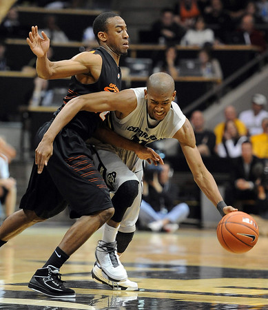 """Cory Higgins of Colorado gets pressured by Markel Brown of Oklahoma State  during the first half of the January 15, 2011 game in Boulder.<br /> For more photos of the game, go to  <a href=""""http://www.dailycamera.com"""">http://www.dailycamera.com</a>.<br /> Cliff Grassmick / January 15, 2011"""