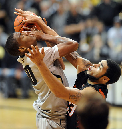 Alec Burks of Colorado gets his shot blocked by Marshall Moses of Oklahoma State during the second half of the January 15, 2011 game in Boulder.<br /> Cliff Grassmick / January 15, 2011