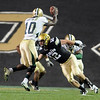 Patrick Mahnke (12) of CU, tries to get his hands on Robert Griffin III of Baylor.<br /> Cliff Grassmick / October 16, 2010