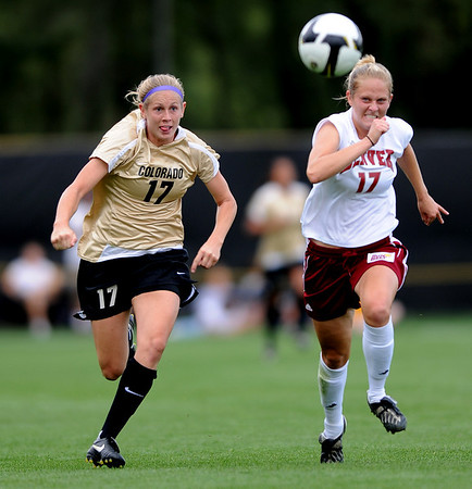 Nikki Marshall, left, of CU and Emily Stewart of Denver University, chase down a ball during the game on Friday night.<br /> Cliff Grassmick / September 4, 2009