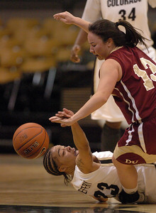 Chucky Jeffery, bottom, of CU and Emiko Smith of Denver, battle for the ball on Wednesday.  Cliff Grassmick / December 2, 2009