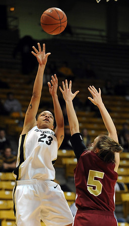 Chucky Jeffery of CU shoots over Britteni Rice of DU.<br /> Cliff Grassmick / December 2, 2009