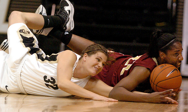 Kelly Jo Mullaney, left, of CU, and Ashley Robinson of Denver, go to the floor to get the ball.<br /> <br /> Cliff Grassmick / December 2, 2009