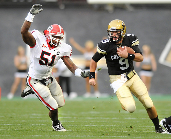 "University of Colorado quarterback Tyler Hansen avoids a tackle by Georgia defender Akeem Dent while rushing the ball during the football game against University of Georgia on Saturday, Oct. 2, at Folsom Field. For more photos go to  <a href=""http://www.dailycamera.com"">http://www.dailycamera.com</a><br /> Photo by Jeremy Papasso"