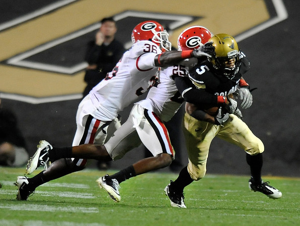 """University of Colorado tailback Rodney Stewart tries to shake a tackle from Georgia defenders Shawn Williams, left, and Vance Cuff, middle, during the football game against University of Georgia on Saturday, Oct. 2, at Folsom Field. The Buffs defeated Georgia 29-27. <br />  For more photos go to  <a href=""""http://www.dailycamera.com"""">http://www.dailycamera.com</a><br /> Photo by Jeremy Papasso"""