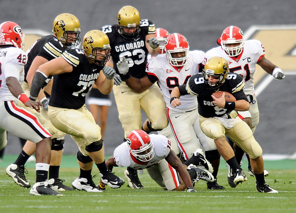"University of Colorado quarterback Tyler Hansen races past a swarm of Georgia defenders while rushing the ball during the football game against University of Georgia on Saturday, Oct. 2, at Folsom Field. For more photos go to  <a href=""http://www.dailycamera.com"">http://www.dailycamera.com</a><br /> Photo by Jeremy Papasso"
