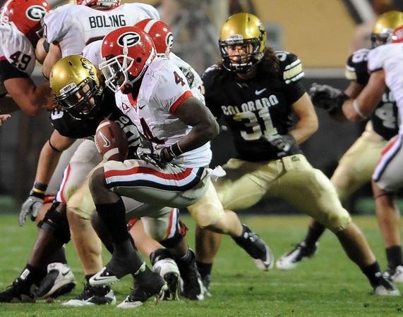 """BJ Beatty of Colorado causes a fumble by Caleb King of Georgia. Jon Major (31) recovered the fumble to stop a possible  game winning drive for Georgia.<br /> For more photos from the game go to  <a href=""""http://www.dailycamera.com"""">http://www.dailycamera.com</a>.<br /> Cliff Grassmick / October 2, 2010"""