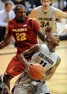 Cory Higgins of CU flies by LaRon Dendy of Iowa State on Saturday. For more  photos of the game, go to www.dailycamera.com. Cliff Grassmick / February 27, 2010