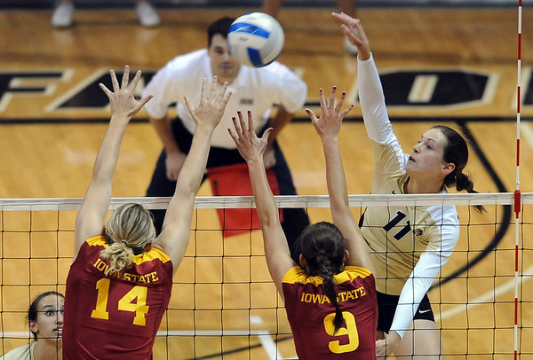 """Rosie Steinhaus of CU hits over Jamie Straube (14) and  Alison Landwehr, of Iowa State.<br /> For more photos of the game, go to  <a href=""""http://www.dailycamera.com"""">http://www.dailycamera.com</a><br /> Cliff Grassmick / October 20, 2010"""