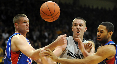 Cole Aldrich, left, and Xavier Henry, both of KU, try to get the ball from Shane Harris-Tunks of CU. Cliff Grassmick / February 3, 2010