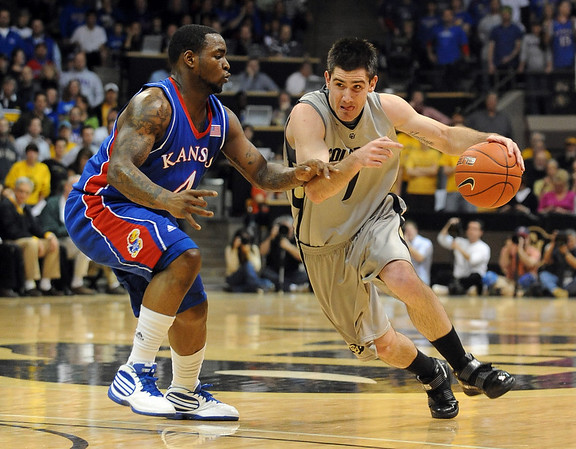 Nate Tomlinson of CU tries to get around Sherron Collins of Kansas.<br /> Cliff Grassmick / February 3, 2010