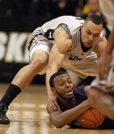 Marcus Relphorde, top, of CU, tries to tie up Jacob Pullen of Kansas State.<br /> Cliff Grassmick / January 16, 2010
