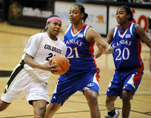 Brittany Spears of Colorado, takes it to the hole past Carolyn Davis and Sade Morris of Kansas.<br /> Cliff Grassmick / February 16, 2010