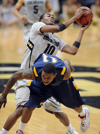 "Carlton Guyton dives in front of Alec Burks of CU.<br /> For more photos of the game, go to  <a href=""http://www.dailycamera.com"">http://www.dailycamera.com</a>.<br /> Cliff Grassmick / March 22, 2011"