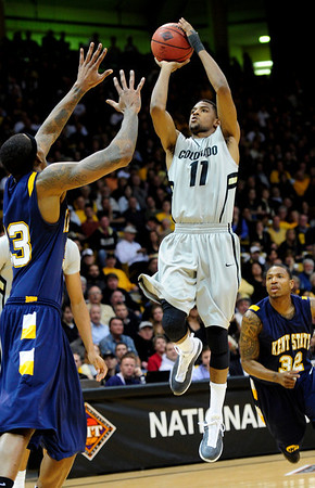 CU's Cory Higgins shoots over Justin Manns of Kent State.<br /> Photo by Marty Caivano/March 22, 2011