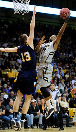 CU's Cory Higgins shoots over Mark Henniger of Kent State.<br /> Photo by Marty Caivano/March 22, 2011