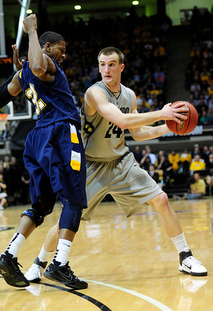 CU's Levi Knutson looks to pass while guarded by Rodriquez Sherman of Kent State.<br /> Photo by Marty Caivano/March 22, 2011