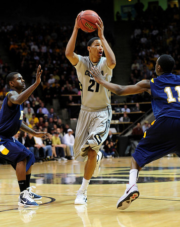 CU's Andre Roberson looks to pass while under pressure from Randal Holt, left, and Carlton Guyton of Kent State.<br /> Photo by Marty Caivano/March 22, 2011